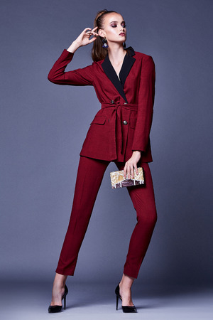 Secretary diplomatic protocol office uniform accessory bag business beautiful woman model fashion style dress perfect body shape brunette hair wear casual formal red suit jacket pants accessory bag.