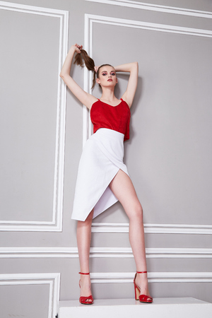 Sexy pretty beautiful woman fashion style clothes model perfect face silk red blouse white skirt high heels shoes glamour model pose interior wall room jewelry accessory catalog beauty salon party. Stock Photo