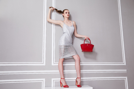 Beautiful young business woman brunette makeup wearing dress grey and high-heeled red shoes accessory bag clothes fun party and walks summer collection perfect body shape interior room wall.