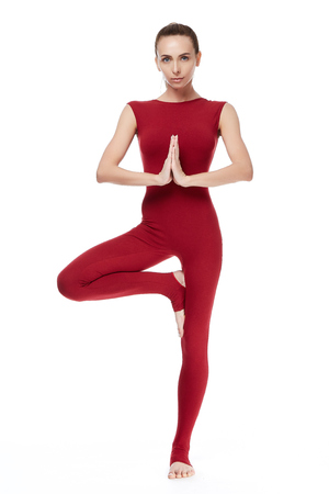 Beautiful sexy blond woman perfect athletic body engaged in yoga, exercise or fitness, lead a healthy lifestyle, dressed in comfortable casual clothes standing in a pose balance relaxes meditation.