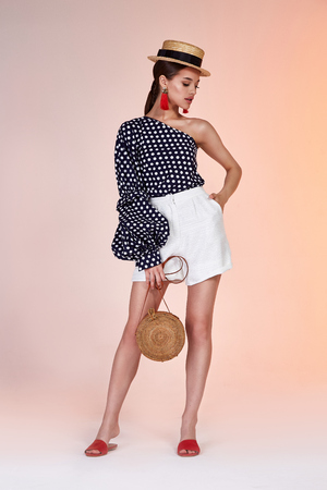 Beautiful sexy woman pretty face long brunette hair wear fashion style clothes blouse short for party walk summer accessory bag straw hat jewelry earrings perfect body skin tan glamour model pose. Stock Photo