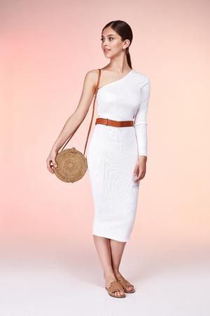 Schöne Frau hübsches Gesicht langes brünettes Haar tragen weiße dünne Kleid Modestil Kleidung für Party Walk Sommerkollektion Zubehör Tasche Gürtel Schmuck Ohrringe Glamour Modell Pose Luxus.