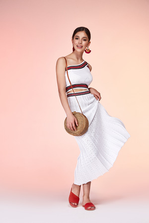 Pretty beautiful sexy elegance woman skin tan body fashion model glamor pose wear white dress casual clothes party summer collection makeup hair style brunette success accessory bag jewelry studio.