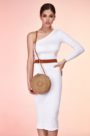 Beautiful woman pretty face long brunette hair wear white skinny dress fashion style clothes for party walk summer collection accessory bag belt jewelry earrings glamour model pose luxury.