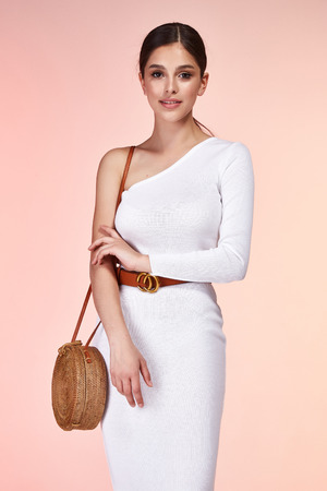 Beautiful sexy woman pretty face long brunette hair wear white skinny dress fashion style clothes for party walk summer collection accessory bag belt jewelry earrings glamour model pose luxury.
