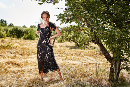 Beautiful young sexy woman long hair bright makeup nature background landscape dry spike grass and trees garden summer model dressed in black lace dress accessory apple romantic date sun sine. Stock Photo