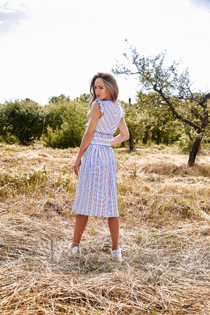 Beautiful young sexy woman long hair bright makeup nature background landscape dry spike grass and apple trees garden summer model wear in light white cotton dress accessory village holiday travel. Stock Photo