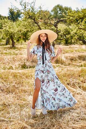 Sexy beautiful young woman fashion model wear long blue stylish dress from summer collection accessory straw hat hot nature garden walk dry grass romance pretty face long brunette hair tan sun shine. Stock Photo