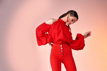 Pretty beautiful sexy elegance woman fashion model glamor pose wear red color trousers silk blouse clothes for party summer collection makeup hair style brunette success accessory bag jewelry studio. Stock Photo