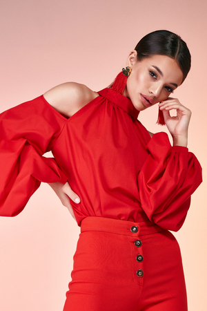 Pretty beautiful sexy elegance woman fashion model glamor pose wear red color trousers silk blouse clothes for party summer collection makeup hair style brunette success accessory bag jewelry studio. Фото со стока