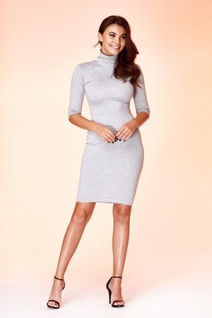 Piękna kobieta modelka nosić stylowe modne ubrania z naturalnej wełny organicznej bawełnianej szarej sukience na co dzień formalny styl biurowy do pracy spotkanie spacer impreza brunetki makijaż włosów.