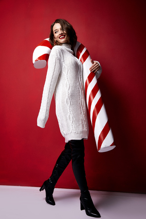 Beautiful young pretty woman with a bright evening make-up of shiny red lipstick on the lips brunette hair festive mood knitted sweater winter Merry Christmas New Year and gift surprise candy cane.