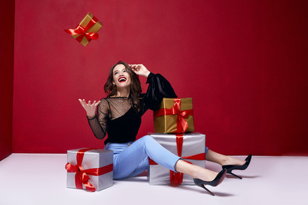 Beautiful young pretty woman with a bright evening make-up of shiny red lipstick on the lips brunette curly hair festive mood winter Christmas New Year St. Valentine's Day and birthday gift surprise. Imagens