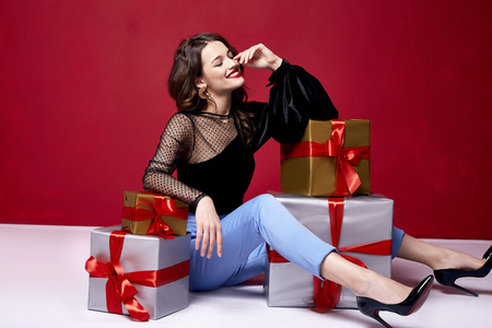 Beautiful young pretty woman with a bright evening make-up of shiny red lipstick on the lips brunette curly hair festive mood winter Christmas New Year St. Valentine's Day and birthday gift surprise. Stock Photo
