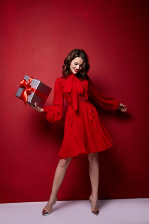 Beautiful young woman thin slim figure evening makeup fashionable stylish dress clothing collection, brunette, gifts boxes red silk bows holiday party birthday New Year Christmas Valentine's Day.