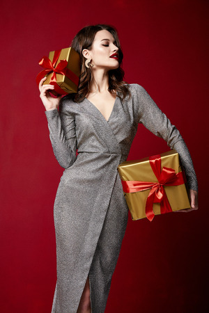 Beautiful sexy young brunette woman hair bright evening make-up red lips long fluffy eyelashes hold gift box holiday New Year  joy fun happy merry Christmas Eve party celebration St. Valentine's Day. Stock Photo