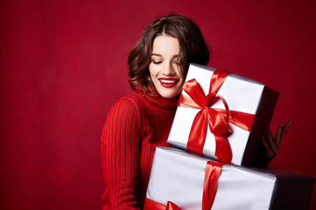 Beautiful young brunette girl with wavy hair bright evening make-up red lips long fluffy eyelashes hold gift box holiday New Year joy fun happy merry Christmas Eve party celebration.