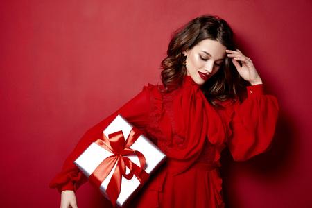 Mooie jonge vrouw dun slank figuur avond make-up modieuze stijlvolle kleding kleding collectie, brunette, geschenken dozen rode zijden strikken vakantie feest verjaardag Nieuwjaar Kerstmis Valentijnsdag. Stockfoto
