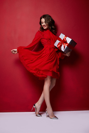 Beautiful young sexy woman thin slim figure evening makeup fashionable stylish dress clothing collection, brunette, gifts boxes red silk bows holiday party birthday New Year Christmas Valentine's Day. Stock Photo