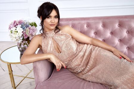Beautiful sexy brunette woman wear fashion gold long maxi dress for party go out ceremony clothes evening seat on the sofa in interior background perfect makeup model hair do luxury life style.