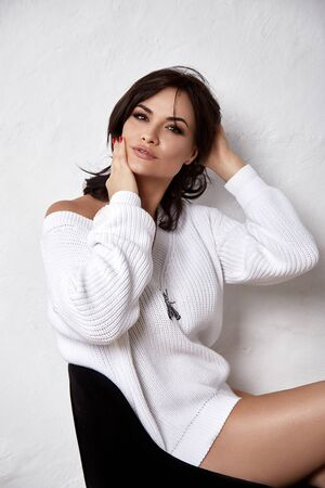 Portrait of brunette sexy beautiful woman shoulder wear cozy knitted white color sweater pretty face skin care tan make up closeup lashes home style fashion dress casual style. 写真素材