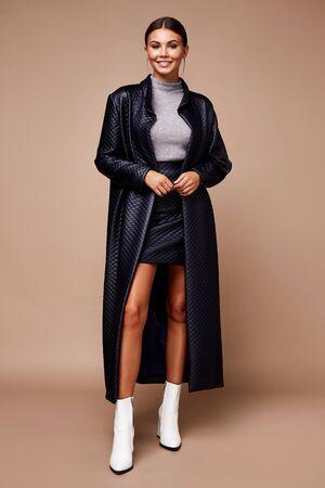 Belle jeune femme dame élégante jupe en mousse élégante trench-coat maquillage et coiffure pour la soirée d'affaires réunion de marche date designer avec accessoires mousse noir talons hauts peau bronzée. Banque d'images