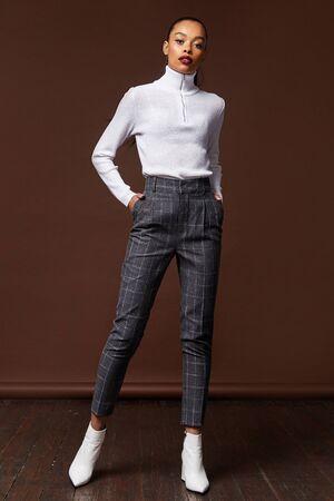Belle femme brune cheveux longs modèle glamour porter un pantalon et un pull travail bureau style code vestimentaire accessoire bijoux studio fond mode fête réunion date maquillage magasin de cosmétiques.
