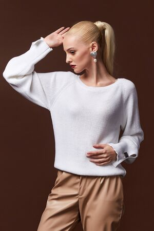 Sexy beautiful woman fashion glamour model blond hair makeup wear sweater lather trousers clothes for every day casual party style accessory date walk girl skinny body shape studio.
