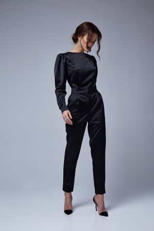 Beautiful sexy young business woman brunette hair evening makeup wearing dress black suit jacket trousers high heels shoes business clothes for meetings walks fall collection perfect body shape.