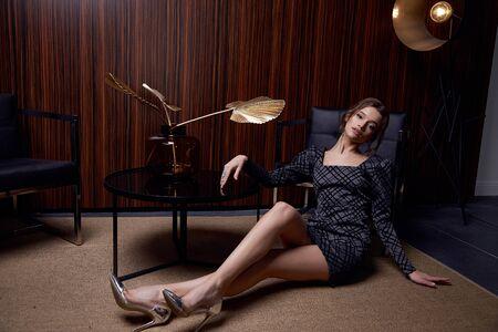 Piękna młoda ładna kobieta jasny makijaż wieczorowy błyszczący czerwona szminka brunetka kręcone włosy nosić elegancką sukienkę moda biżuteria buty na obcasie ubrania dla strony spotkanie wnętrze pokoju. Zdjęcie Seryjne