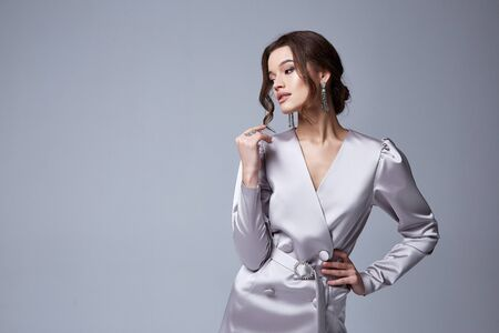 Beautiful sexy young business woman brunette hair with evening makeup wearing a dress white silk and high-heeled shoes  fashion clothes for date party romantic collection perfect body shape.