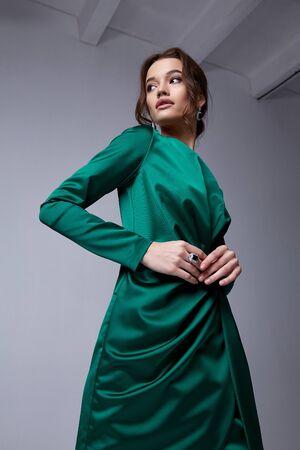 아름 다운 젊은 여자 얇은 슬림 그림 저녁 메이크업 유행 세련 된 드레스 의류 컬렉션, 갈색 머리, 녹색 실크 리본 휴일 파티 생일 새 해 크리스마스 발렌타인 데이.