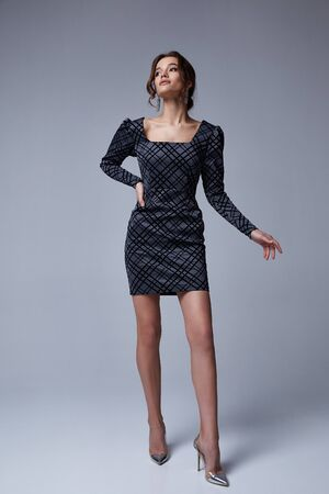 Beautiful sexy brunette woman business office style fashion clothes fall collection perfect body shape pretty face makeup smile wear grey dress skinny casual accessory glamour model.