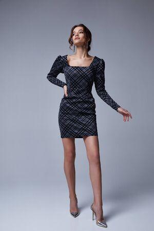 Mooie brunette vrouw zakelijke kantoorstijl mode kleding herfst collectie perfecte lichaamsvorm mooi gezicht make-up glimlach draag grijze jurk skinny casual accessoire glamour model.