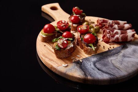 Exclusive painted art cutting board made of wood organic serving dishes with taste food cuisine delicious toast with cream cheese arugula tomato meat dry jerky.