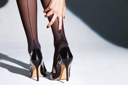 Part of woman body perfect shape legs feet skin tan wear stockings, nylons, pantyhose lingerie hosiery hose studio shot. on white background high heels.