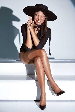 Sexy pretty woman perfect body shape wear black skinny body shirt, hat, stockings, nylons, pantyhose high heels in white studio background lights shadow beautiful fashion model tan skin.
