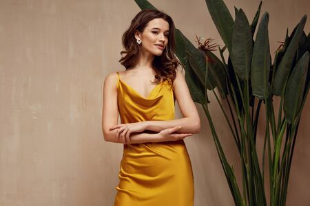 Portrait of beautiful woman fashion model brunette hair wear yellow silk dress accessory jewelry earrings cosmetic face clothes romantic date party walk summer collection tanned skin green leaves.