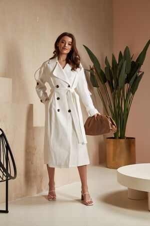 Beautiful brunette woman natural make up wear fashion clothes casual dress code office style white long cloak for romantic date business meeting accessory bag lather interior boho stairs flowerpot.