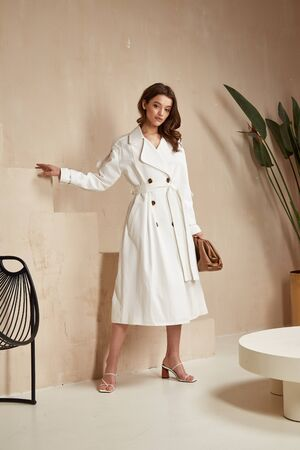 Beautiful brunette woman natural make up wear fashion clothes casual dress code office style white long cloak for romantic date business meeting accessory bag lather interior boho stairs flowerpot. Stock Photo