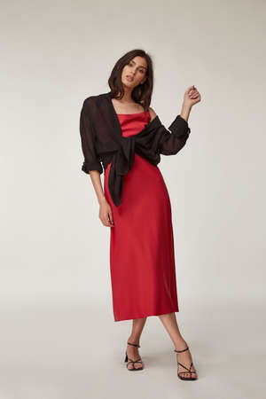 Fashion pretty woman beautiful makeup perfect body shape tanned skin wear clothes summer collection organic textile black cotton cape, light gray suit crop top and trousers stylish sandals shoes. Foto de archivo