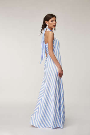 Sexy fashion model beautiful woman pretty face natural makeup, tanned skin body wear summer collection clothes style for romantic date light silk in white blue stripes long midi dress earrings. Stock fotó