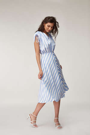 Sexy fashion model beautiful woman pretty face natural makeup, tanned skin body wear summer collection clothes style for romantic date walk casual trendy light silk in white blue stripes long dress. Stock fotó