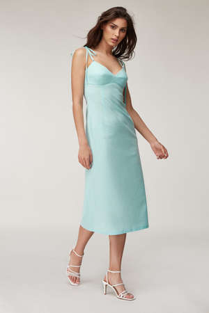 Woman beautiful face natural make up brunette hair tanned skin body wear fashion summer collection organic cotton long light blue skinny dress style for romantic date walk, accessory shoes sandals.