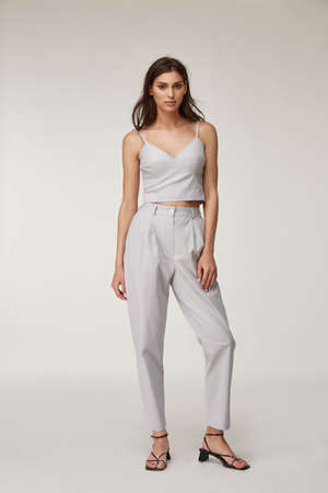Fashion pretty woman beautiful makeup perfect body shape tanned skin wear clothes summer collection organic textile cotton light gray suit crop top and trousers stylish sandals shoes. Stock fotó