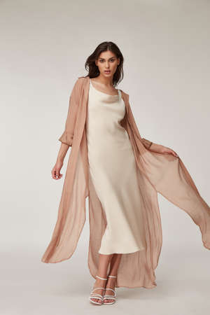 Beautiful woman fashion model makeup brunette hair perfect body shape tanned skin wear clothes summer collection organic silk dress and long shirt cape stylish sandals shoes, accessory romantic. Stock fotó