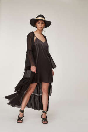 Fashion pretty woman beautiful makeup perfect body shape tan skin wear clothes summer collection organic black cotton cape, silk short dress stylish sandals shoes, accessory hat and jewelry earrings.