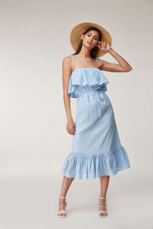 Woman beautiful face natural make up brunette hair tanned skin body wear fashion summer collection organic cotton lace long blue dress style for romantic date walk, accessory and shoes sandals hat.