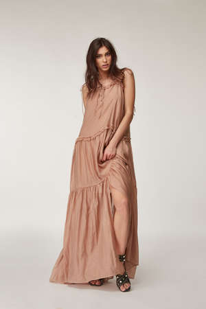 Beautiful woman fashion model makeup brunette hair perfect body shape tanned skin wear clothes summer collection organic long beige silk dress stylish sandals shoes, accessory jewelry earrings date.