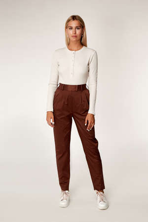 Sexy beautiful woman fashion glamor model blond hair makeup wear white long sleeve skinny blouse on button cotton trousers clothes for every day casual style accessory date walk body shape studio.